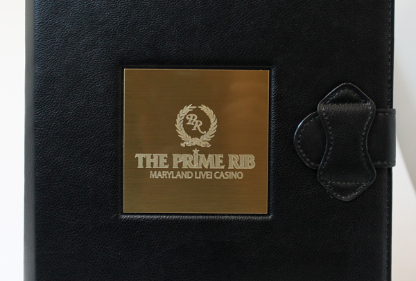 Custom cut metal plate diamond engraved with logo and adhered to leather menu.
