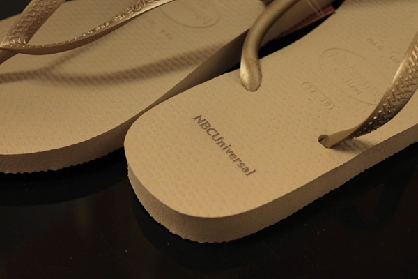 Havaianas flip flops branded by laser engraving NBCUniversal logo.